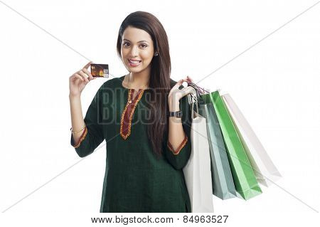 Portrait of a happy woman holding shopping bags and credit card