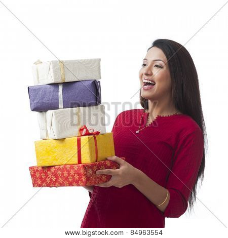 Happy woman holding stack of gifts and smiling