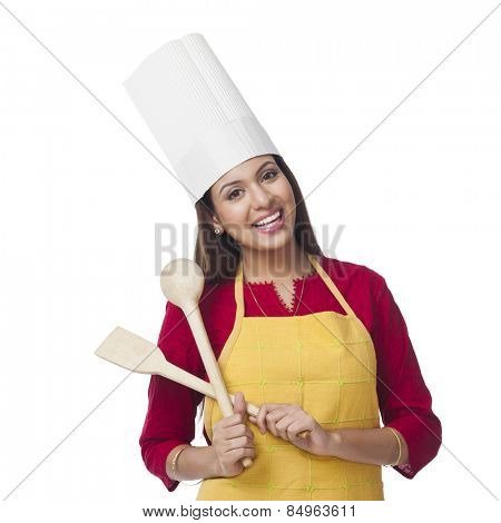 Portrait of a happy woman holding a spatula and ladle