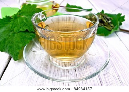 Tea with sage in cup on light board
