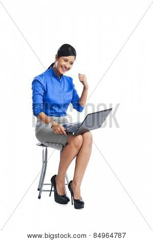 Businesswoman looking excited while sitting on a stool and using a laptop