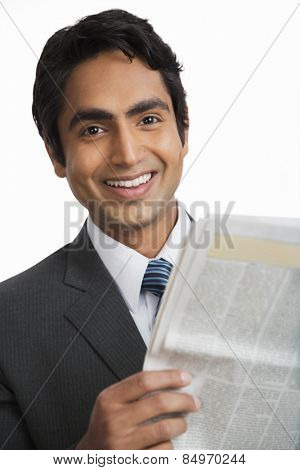 Portrait of a businessman reading a newspaper and smiling