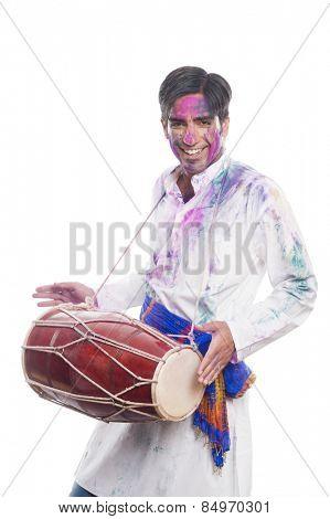 Man celebrating Holi with playing dholak