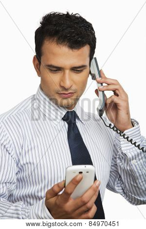 Businessman talking on a landline phone while looking at a mobile