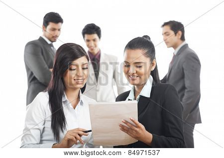 Two businesswomen reading a document with their colleagues in the background