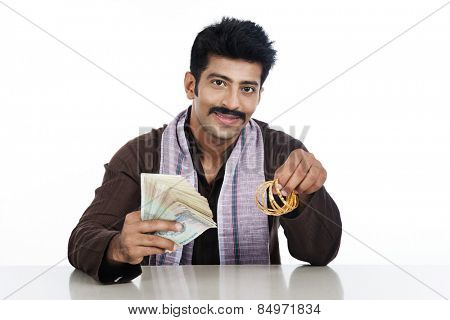 Portrait of a man holding money and golden bangles