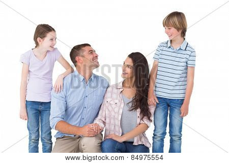 Family smiling while looking at each other over white background