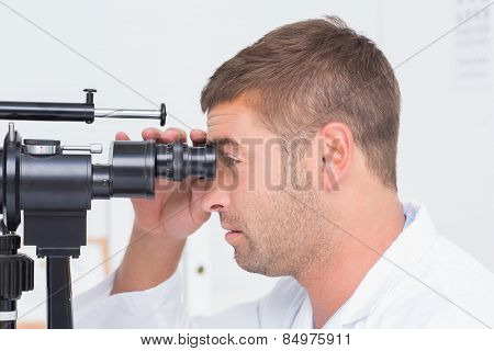 Side view of optician using slit lamp in clinic