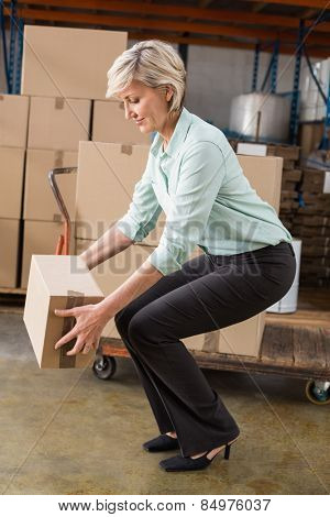Warehouse manager picking up cardboard box in a large warehouse