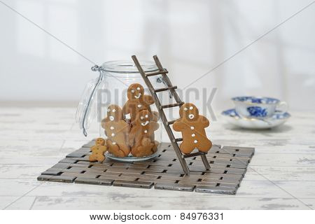 Gingerbread man climbing ladder into cookie jar