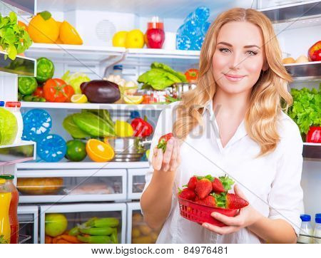 Portrait of cute blond woman standing near open refrigerator full of fruits and vegetables and eating fresh red ripe strawberries