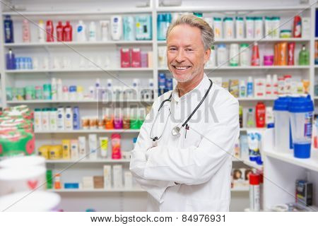 Pharmacist in lab coat with stethoscope and arms crossed in the pharmacy