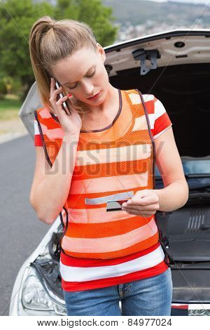 Young woman calling with her mobile phone beside her broken down car