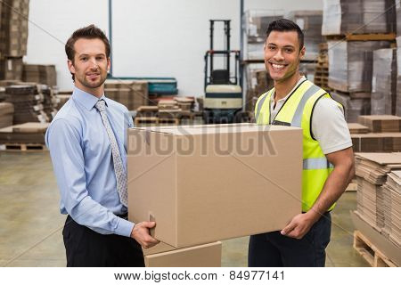 Warehouse worker and manager passing a box in a large warehouse