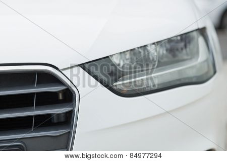 Close up of a headlight of a white car