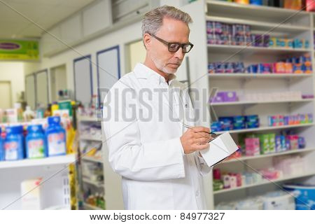 Focused pharmacist writing on box of medicine at the pharmacy