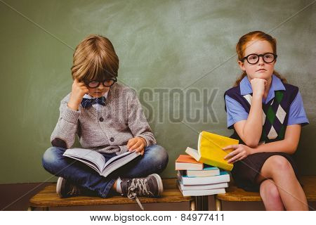 Little school kids with stack of books in classroom