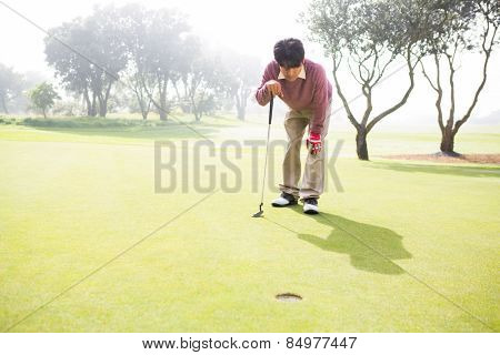 Golfer looking at the hole at the golf course