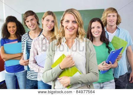 Portrait of happy college students holding folders at college