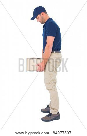 Full length side view of delivery man carrying heavy package on white background