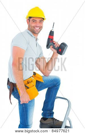 Portrait of confident handyman holding power drill while climbing ladder on white background
