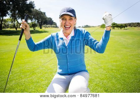 Kneeling lady golfer cheering on putting green on a sunny day at the golf course