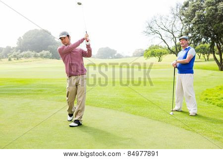 Golfer swinging his club with friend behind him at the golf course