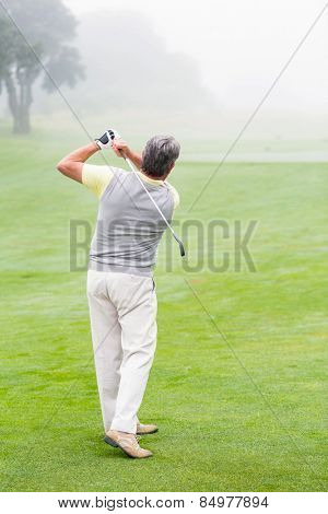 Golfer swinging his club on the course on a foggy day at the golf course
