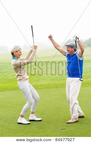 Cheering golfing couple on a foggy day at the golf course