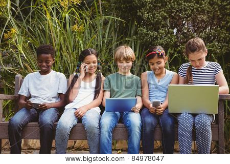 View of children using technologies at the park