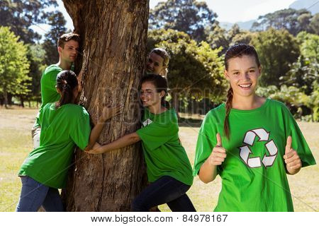 Environmental activists hugging a tree in the park on a sunny day