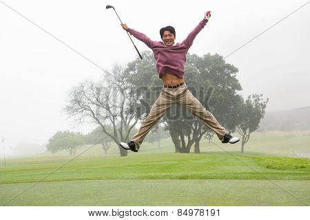 Excited golfer jumping up and smiling at camera at the golf course