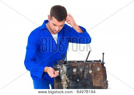 Confused mechanic repairing car engine over white background