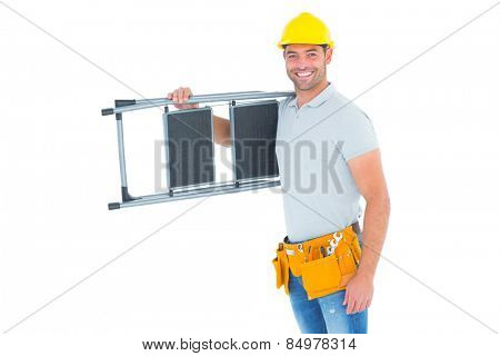 Portrait of happy manual worker carrying step ladder on white background
