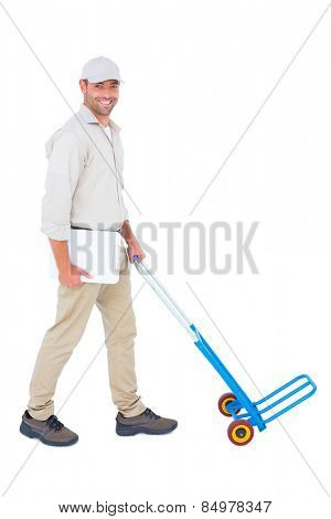 Full length portrait of confident delivery man pushing empty trolley on white background