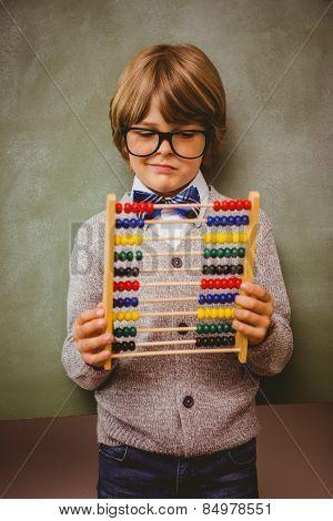 Portrait of cute little boy holding abacus in front of blackboard