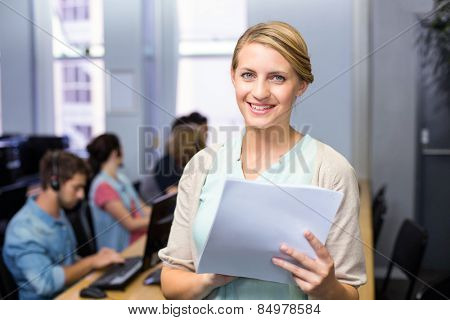 Portrait of female teacher holding document in computer class