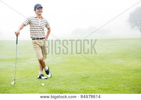 Cheerful golfer holding his club with hand on hip at the golf course