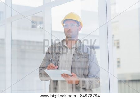 Male architect writing on clipboard while looking through office window