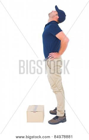 Full length side view of delivery man suffering from back ache on white background