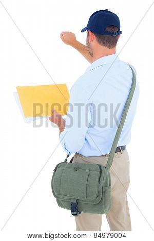 Rear view of postman with letter knocking on white background