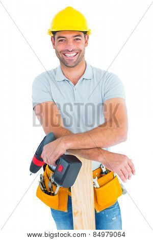 Portrait of smiling male carpenter with power drill and plank on white background