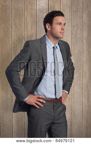 Serious businessman with hands on hips against wooden surface with planks