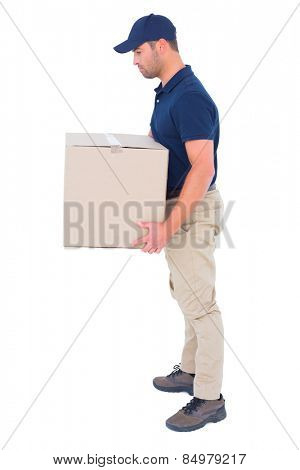 Full length side view of delivery man carrying cardboard box on white background