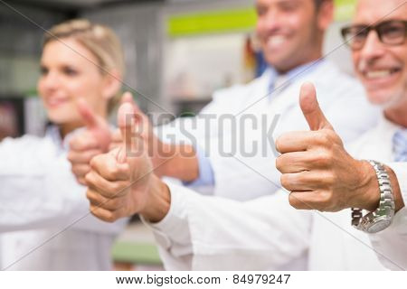 Positive co-workers standing with thumbs up in the pharmacy