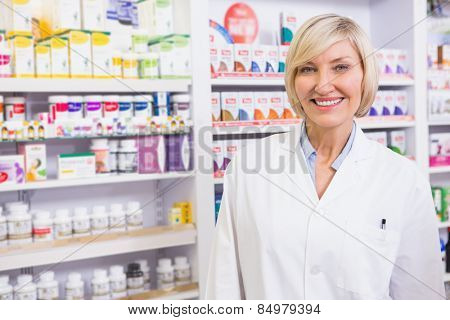 Smiling blonde pharmacist posing in lab coat in the pharmacy