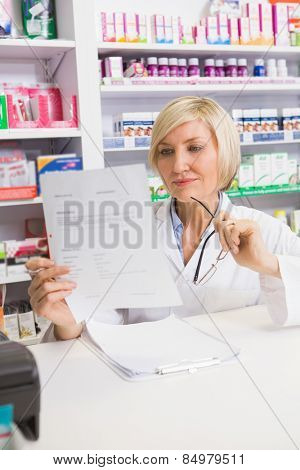 Smiling pharmacist thinking and reading prescription in the pharmacy