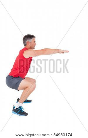 Fit man doing a squat on white background