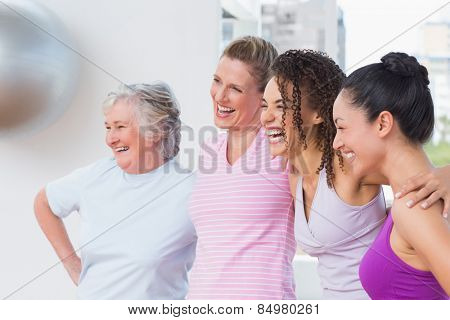 Happy female friends standing arms around in fitness studio