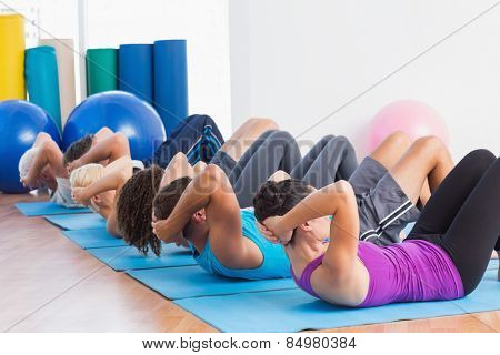 Fit men and women doing sit-ups on exercise mats at fitness club